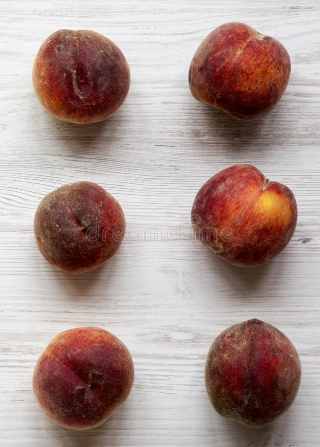 Fresh peaches on white wooden background, top view. Overhead, from above. Close-up stock images
