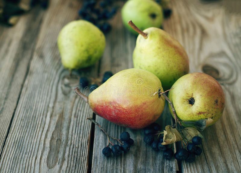 Fresh pears and berries of a black mountain ash. On a wooden background close up. Autumn harvest of fruit stock images