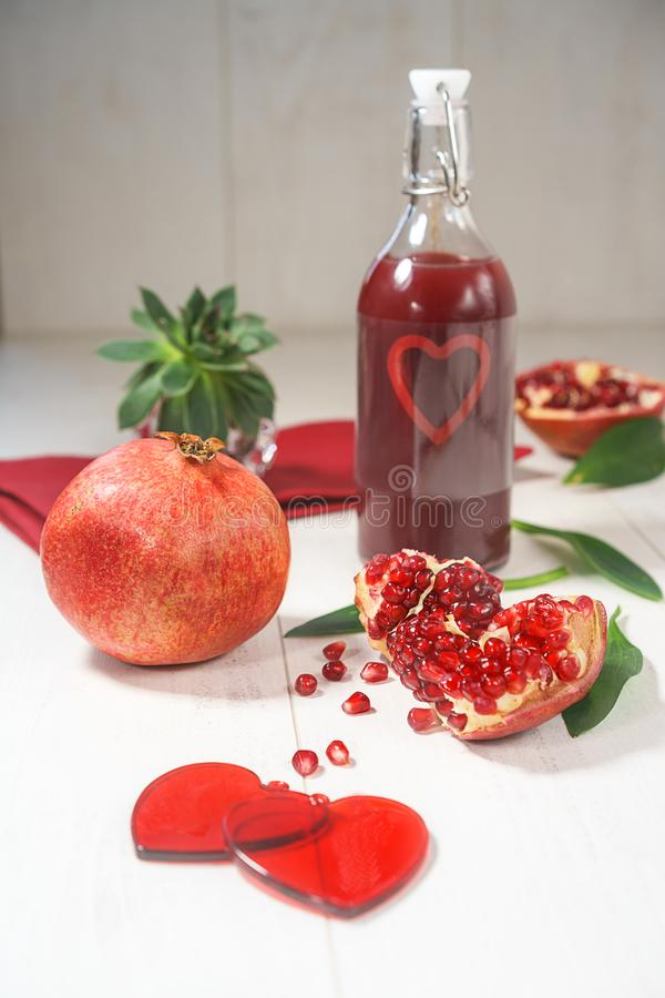 Fresh peeled pomegranates with ruby red beans and two hearts bottle with heart on wooden table background, selective focus, rustic royalty free stock photo