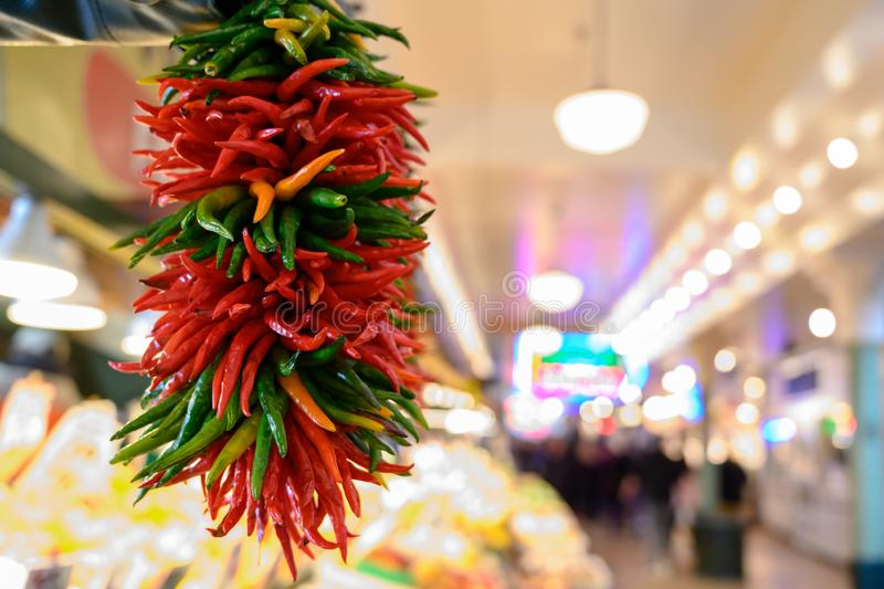 Fresh peppers hanging at market. Fresh peppers hanging for sale at Seattle Washington`s Pike Place Market stock photo