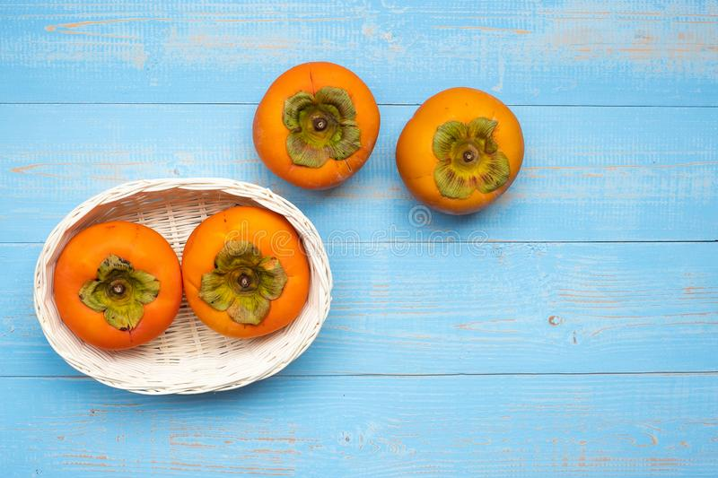 Fresh persimmons in wooden basket on blue table background royalty free stock images
