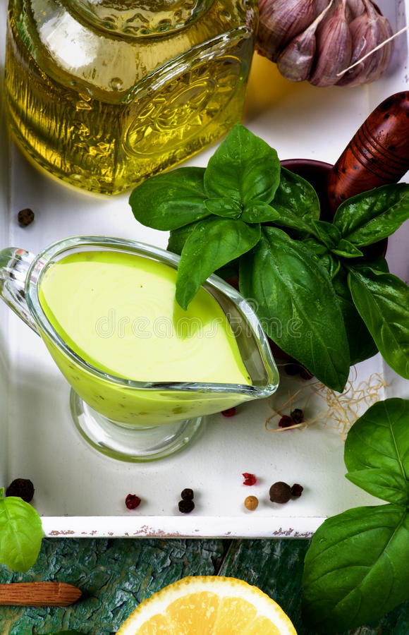 Fresh Pesto Sauce. Freshly Made Creamy Pesto Sauce in Glass Gravy Boat with Fresh Basil Leafs, Raw Ingredients and Olive Oil in White Wooden Tray closeup. Top stock photography
