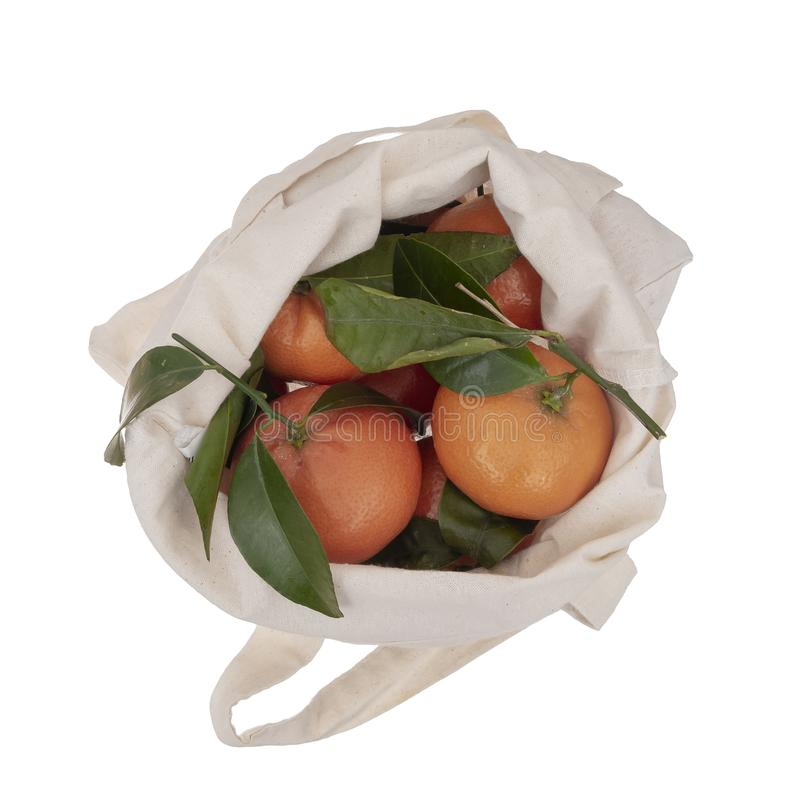 Fresh picked oranges in reusable, recyclable fabric shopping tote bag, isolated on white. For environmentally friendly. Fresh picked oranges in reusable royalty free stock image
