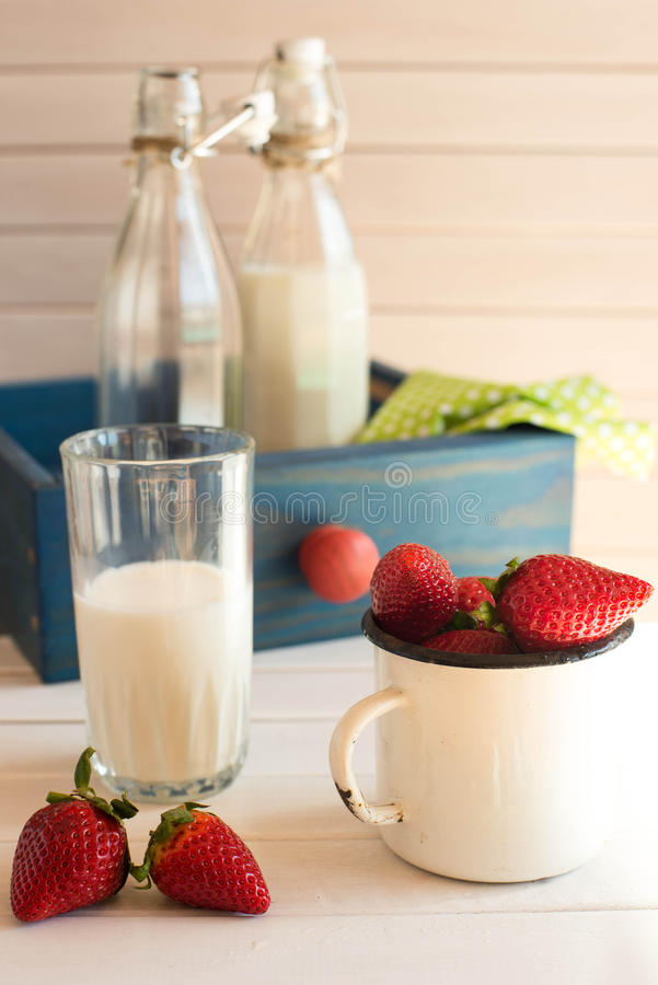 Fresh picked strawberrys with glass of the milk on white wooden background. royalty free stock photos