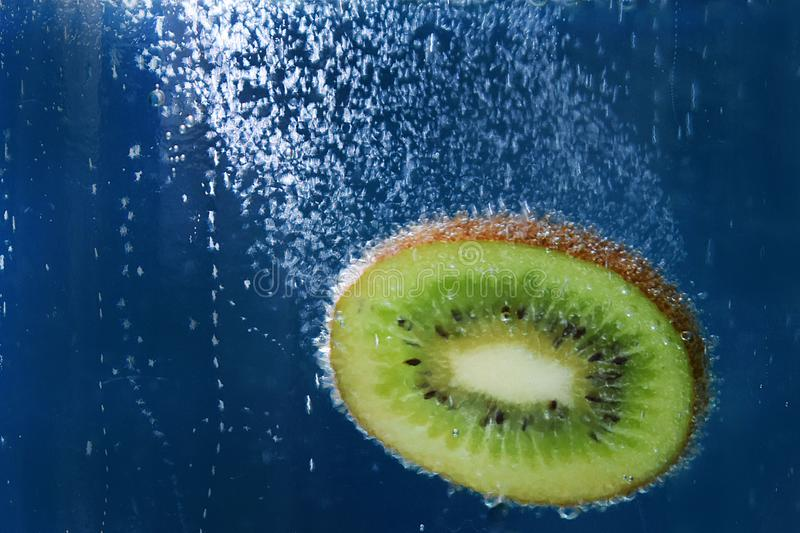 Fresh piece of kiwi falling into the water on a blue background texture closeup macro stock photography