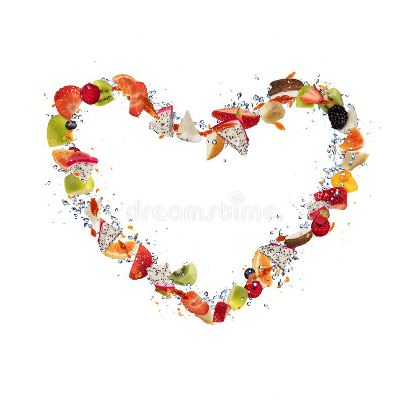 Fresh pieces of fruit flying in heart shape on white. Fresh pieces of fruit flying in heart shape, isolated on white background stock photography