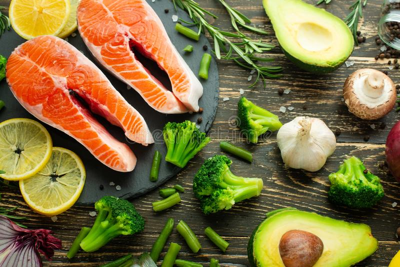 Fresh pieces of salmon steak, trout, salmon, pink salmon. With ingredients vegetables, avocado, rosemary and broccoli. Healthy and stock photos