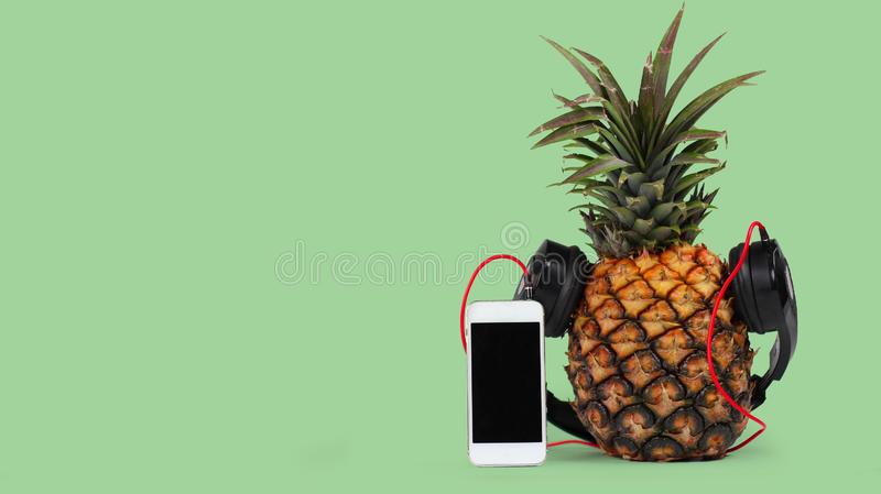 fresh pineapple with black headphones and smartphone with  black screen against green background stock photo