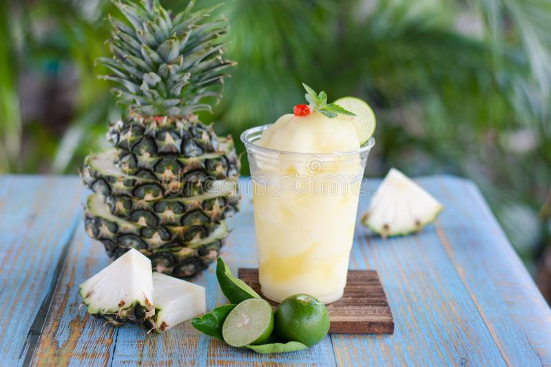 Fresh pineapple frappe in a plastic cup put on blue wood table. royalty free stock photo