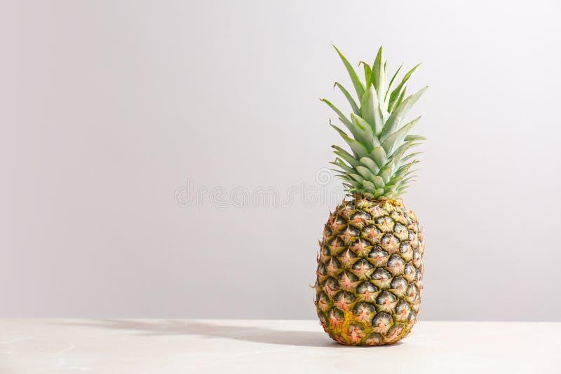 Fresh pineapple on table. Against grey wall stock photos