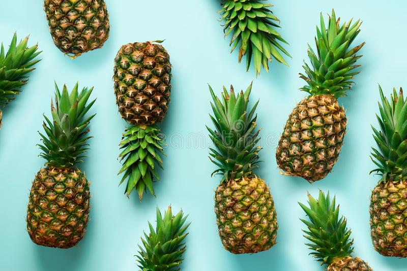 Fresh pineapples on blue background. Top View. Pop art design, creative concept. Copy Space. Bright pineapple pattern stock photos