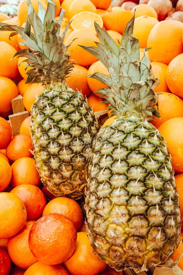 Fresh Pineapples and Oranges for Sale on Market Stall stock images