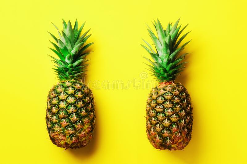 Fresh pineapples on yellow background. Top View. Pop art design, creative concept. Copy Space. Bright pineapple pattern stock image