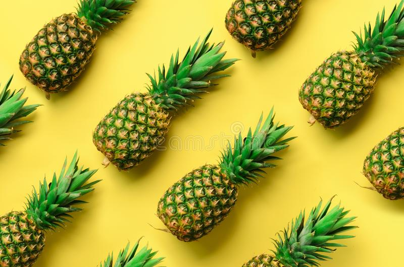 Fresh pineapples on yellow background. Top View. Pop art design, creative concept. Copy Space. Bright pineapple pattern royalty free stock photo