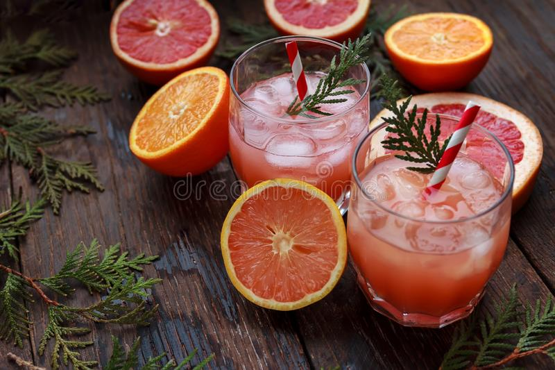 Fresh pink alcoholic cocktail with grapefruit, ice and juice, drink glass on a wooden board, old rustic style, selective stock images