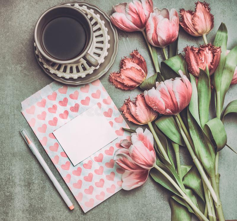 Fresh pink pale tulips flowers with heart letter , blank paper , marker and cup of coffee , top view. royalty free stock photography