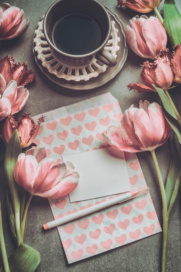 Fresh pink pale tulips with heart , blank paper , marker and cup of coffee , top view. stock photos