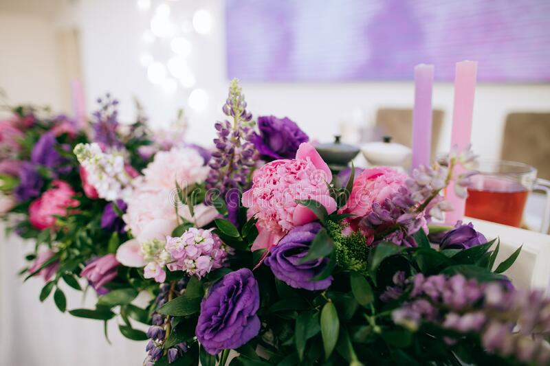 Fresh pink and purple bouquets of flowers on the table of the bride and groom at the restaurant.  royalty free stock image