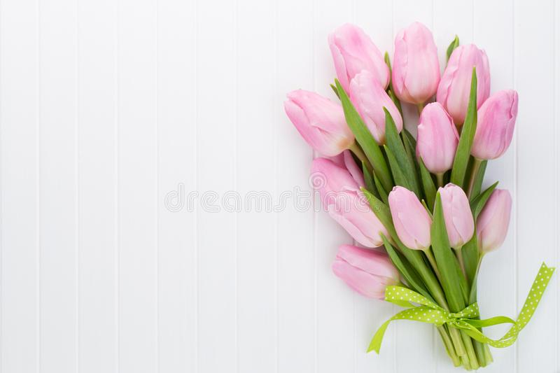 Fresh pink tulip flowers bouquet on shelf in front of wooden wall. stock photos