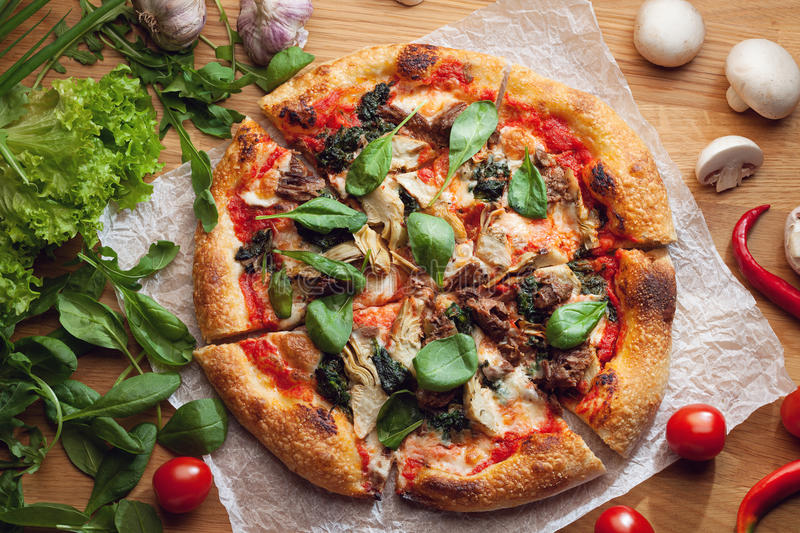 Fresh pizza with ingredients on wooden table royalty free stock images