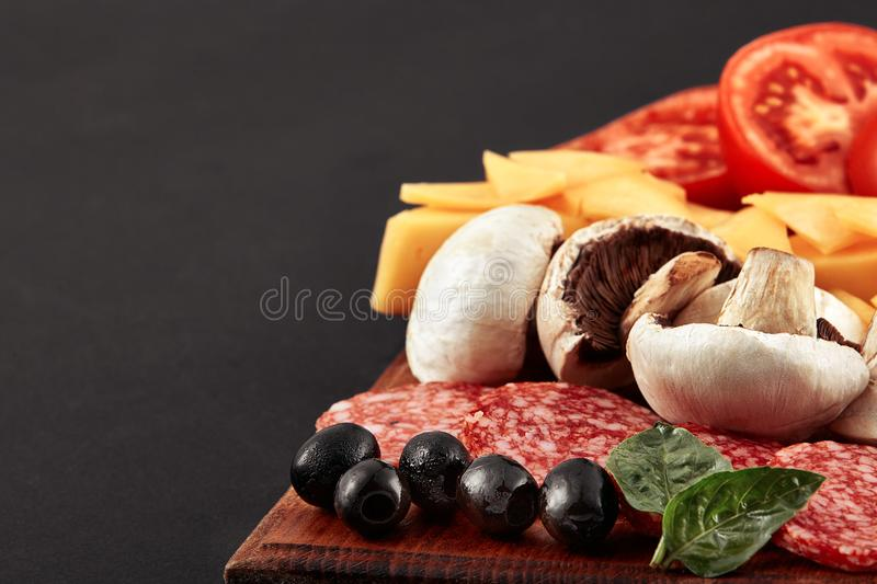 Fresh pizza with tomatoes, cheese and mushrooms on wooden table royalty free stock photo