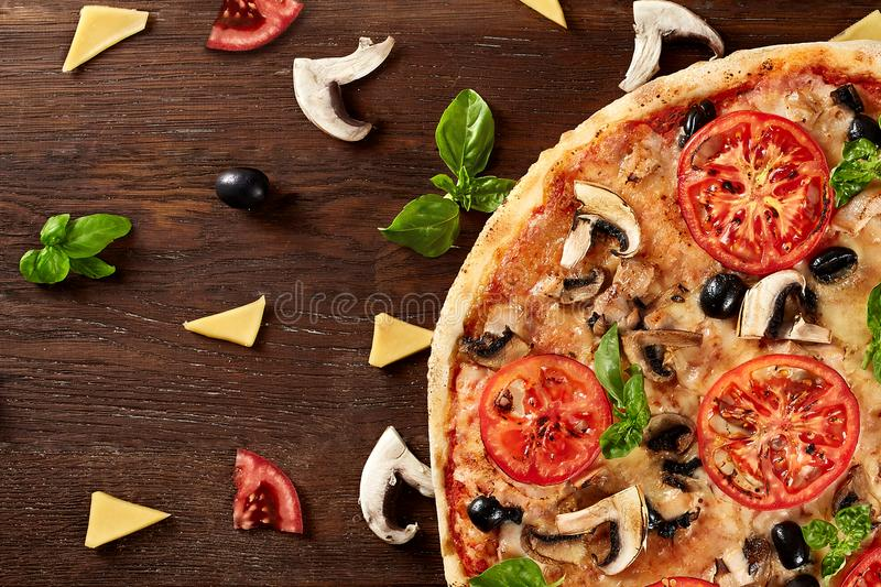 Fresh pizza with tomatoes, cheese and mushrooms on wooden table stock photos