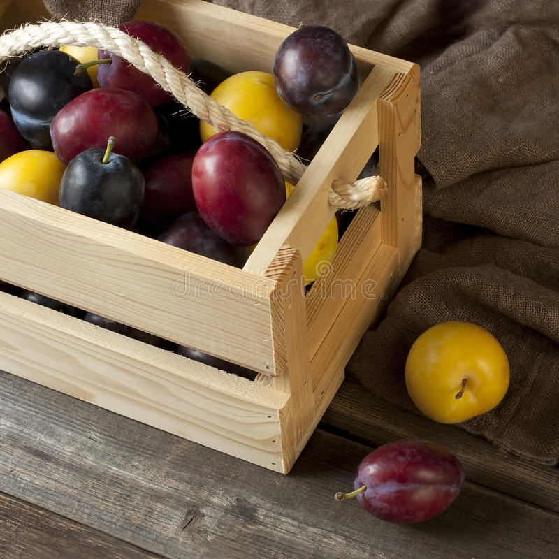Fresh Plums In Box On Wooden Board Stock Photo
