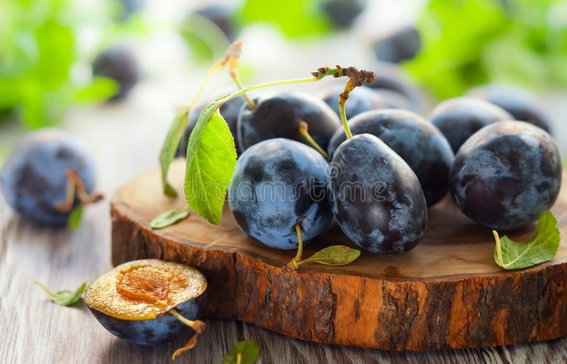 Fresh plums with leaves. On wooden background royalty free stock images