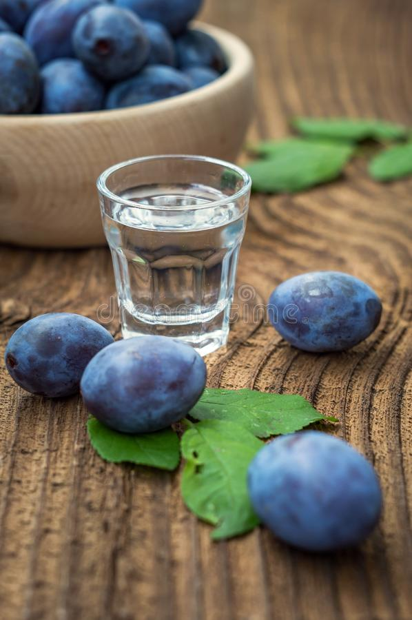 Fresh plums and plum brandy on wood table stock images