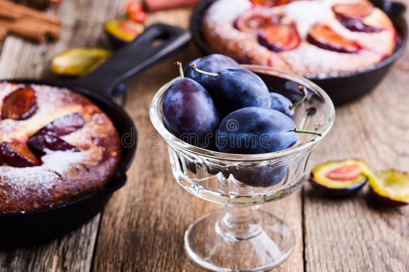 Fresh plums and summer fruit pie. With fresh plums in cast iron skillet on rustic wooden table stock photo