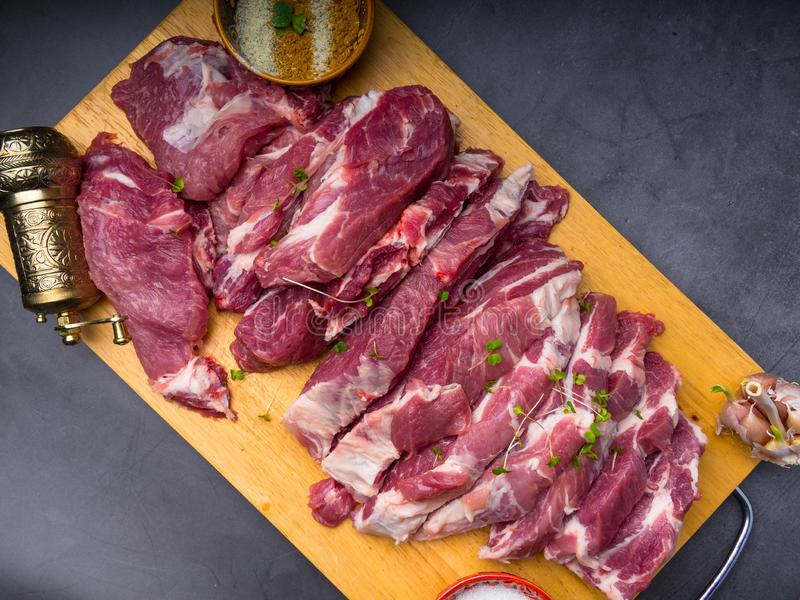Fresh pork with ingredients for cooking on dark background. Fresh pork with ingredients for cooking on dark concrete background stock images