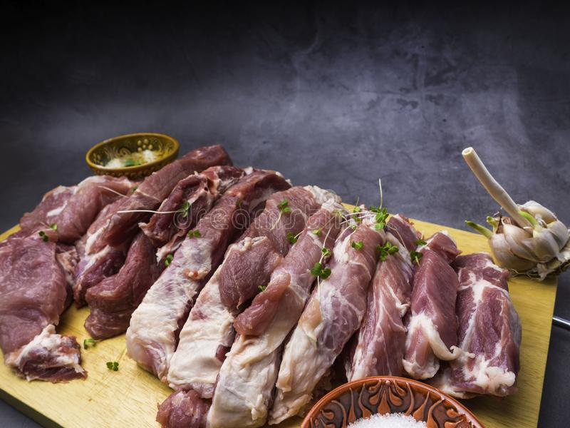 Fresh pork with ingredients for cooking on dark background. Fresh pork with ingredients for cooking on dark concrete background stock image