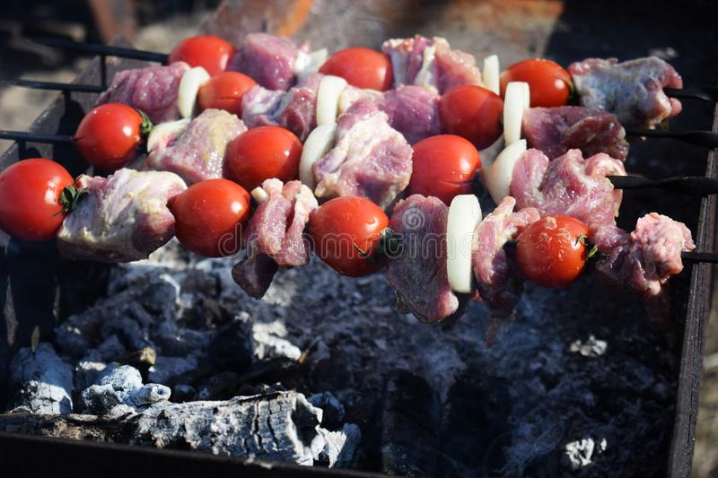 Fresh pork meat with vegetables grilled. Cooking in nature. Juicy shish kebab from pork, tomatoes, fried on a fire outdoor background barbecue skewers summer royalty free stock photography