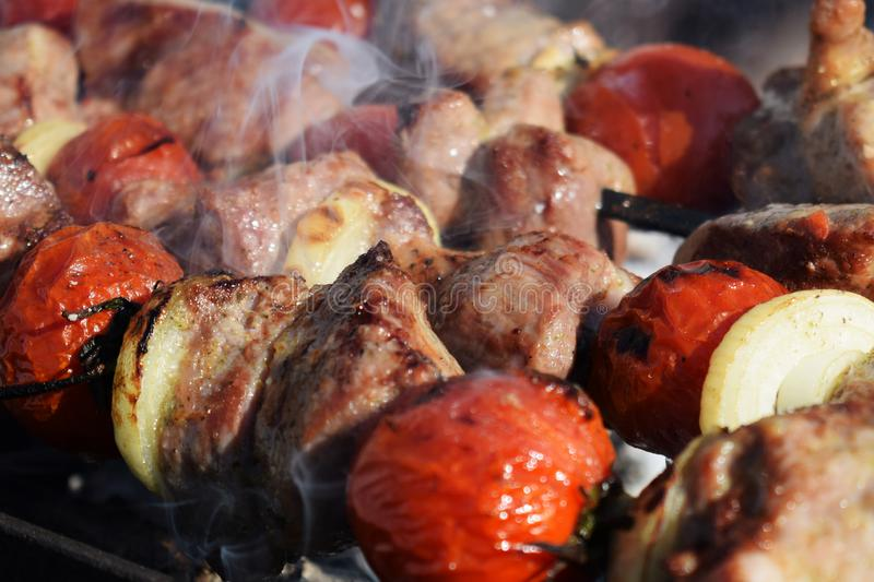 Juicy shish kebab from pork and tomatoes, fried on a fire outdoor. royalty free stock photography