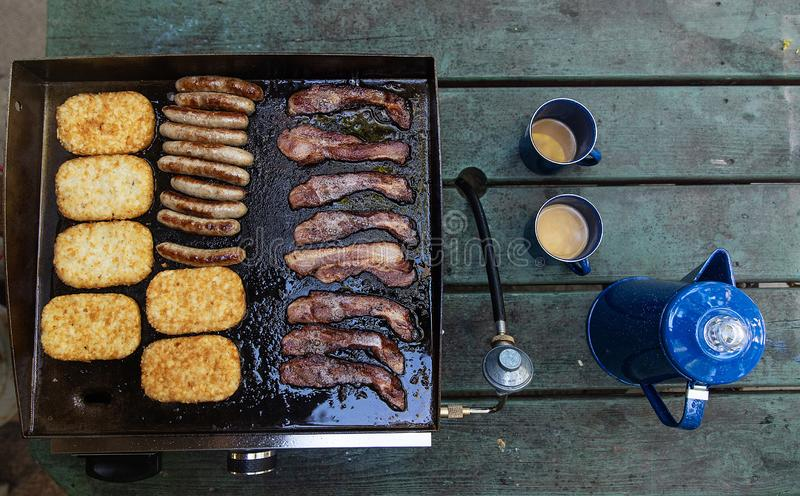 Fresh pot of coffee with bacon, sausage and hashbrowns cooking on a hot grill royalty free stock photos