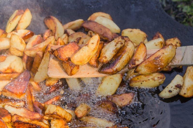 Fresh potato boiled in large restaurant frying pan. Picnic healthy food cooking at large metallic pan stock photo