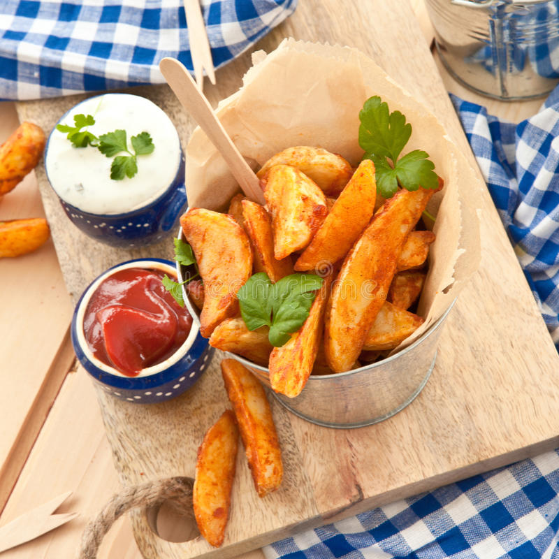 Fresh potato wedges. With sour cream dip royalty free stock image