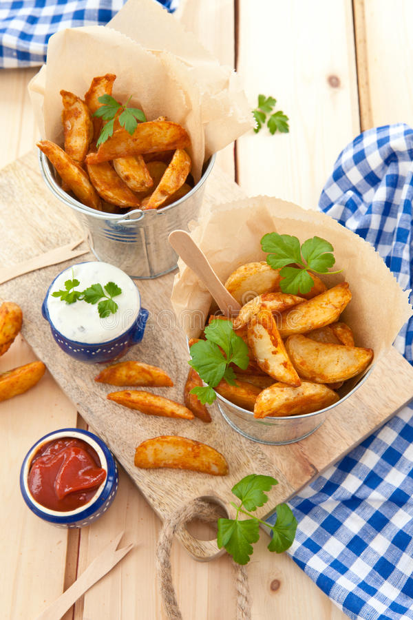 Fresh potato wedges. With sour cream dip royalty free stock images