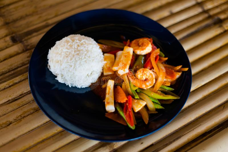 Thai red curry paste seafood. Fresh prepared asian spicy red curry paste seafood mix served with jasmine rice in local restaurant on Koh Lanta island royalty free stock photography