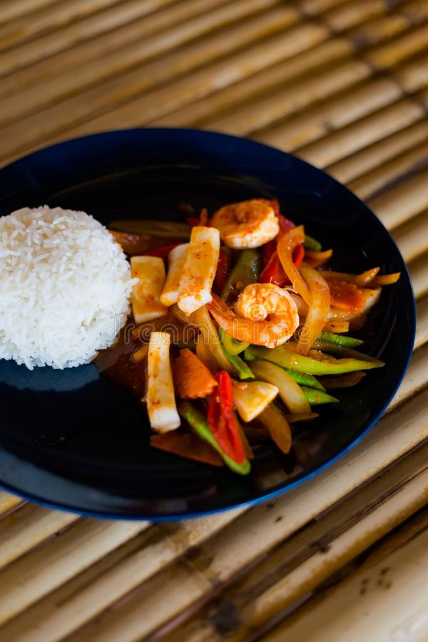 Thai red curry paste seafood. Fresh prepared asian spicy red curry paste seafood mix served with jasmine rice in local restaurant on Koh Lanta island royalty free stock image
