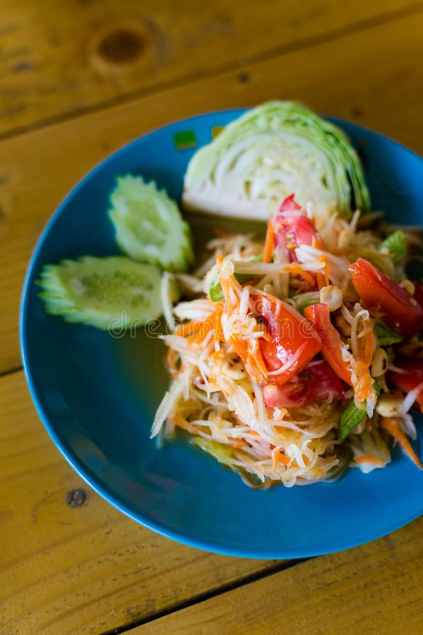 Thai Som Tam papaya salad. Fresh prepared asian spicy Som Tam papaya salad with cabbage and cucumber served in local restaurant on Koh Mook island. Traditional stock images