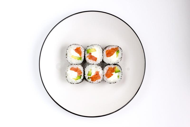 Fresh prepared sushi rolls with avocado, red fish salmon and whit cheese filadelfia on white plate. Top view stock image