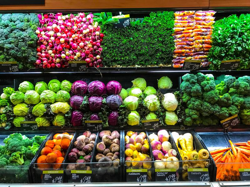 Vegetable Farm Produce on Store Grocery Shelves. Fresh produce of carrots, beets, celery, bok choy, spinach, kale, lemon grass, radios, broccoli, cilantro stock photo
