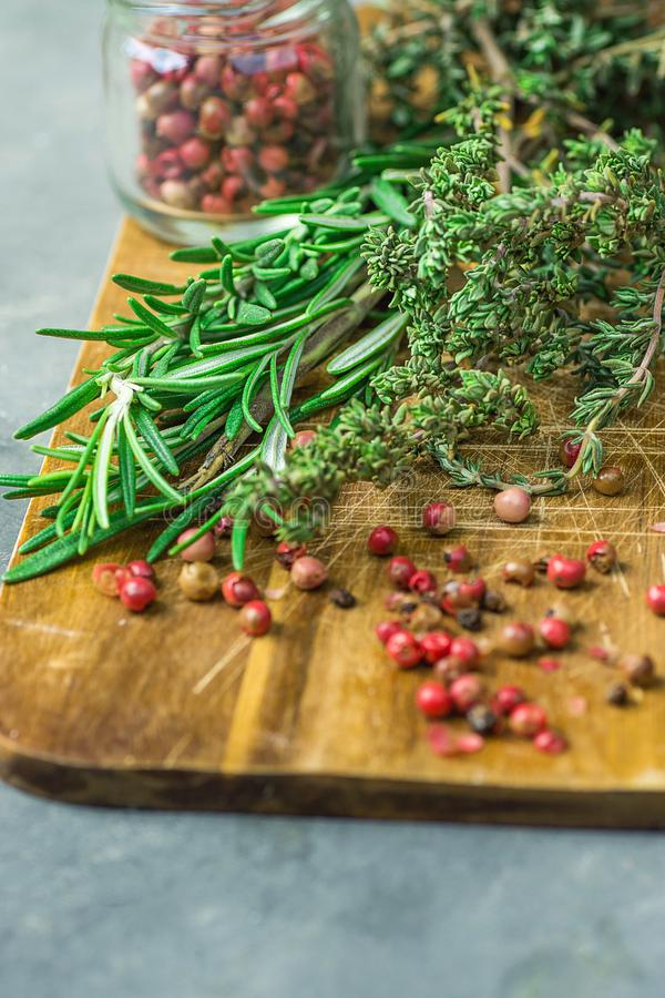 Fresh Provence Herbs Rosemary Thyme Twigs red Pink Peppers in Glass Jar on Aged Wood Cutting Board Knife on Dark Table. Fresh Provence Herbs Rosemary Thyme Twigs stock image