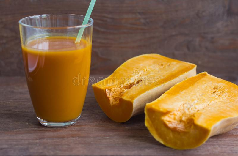 Fresh pumpkin juice and pumpkin on wooden background,delicious autumn drink royalty free stock photo