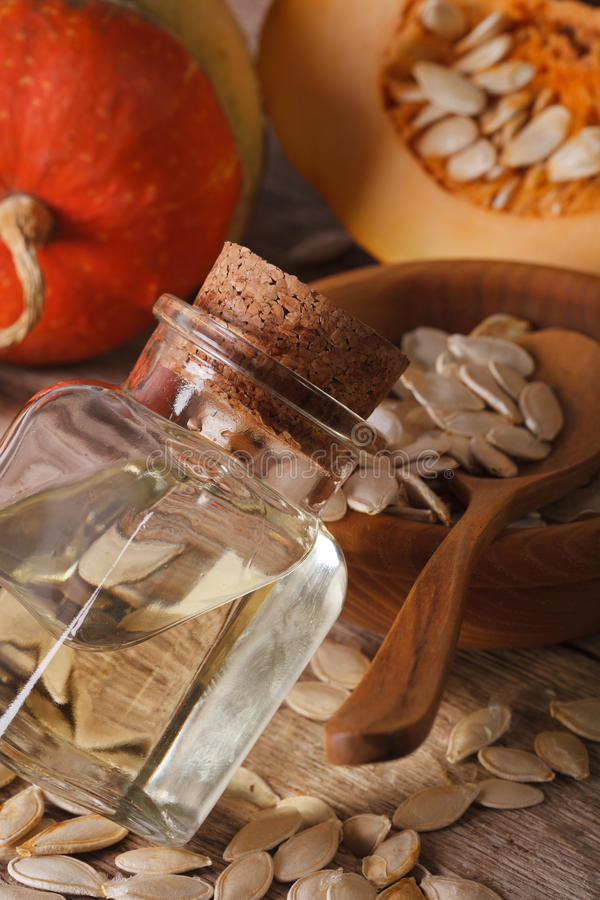 Fresh pumpkin seed oil in a bottle macro on the table. vertical stock photography