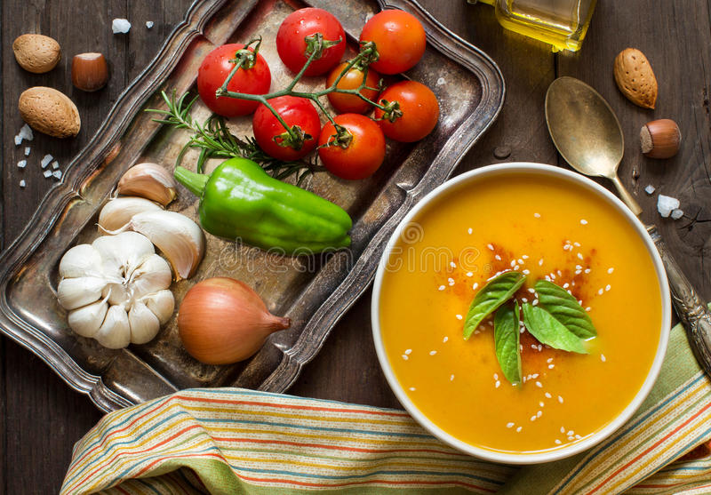 Fresh pumpkin soup and vegetables on a wooden table royalty free stock image