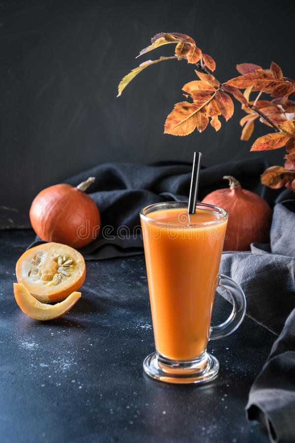 Fresh pumpkin smoothie or juice on dark. Autumn, fall or winter hot drink. Cozy healthy beverage. Fresh pumpkin spice smoothie or juice on dark. Autumn, fall or royalty free stock photography