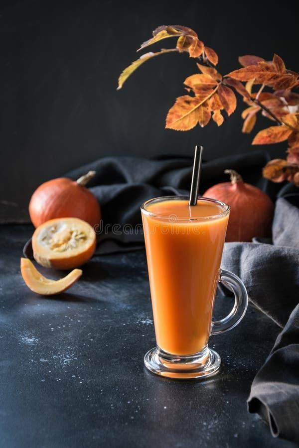 Fresh pumpkin spice smoothie or juice on dark. Autumn, fall or winter hot drink on dark. Cozy healthy beverage. Fresh pumpkin spice smoothie or juice on dark stock images