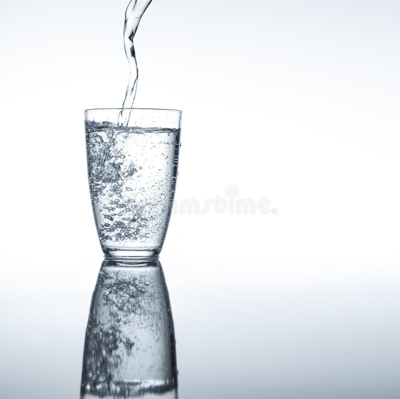 Fresh pure water. Moment in which pure sparkling water is poured into a glass royalty free stock photography